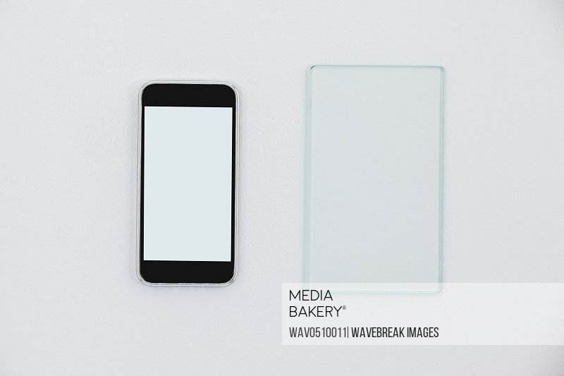 Close-up of sheet of glass and mobile phone on white background