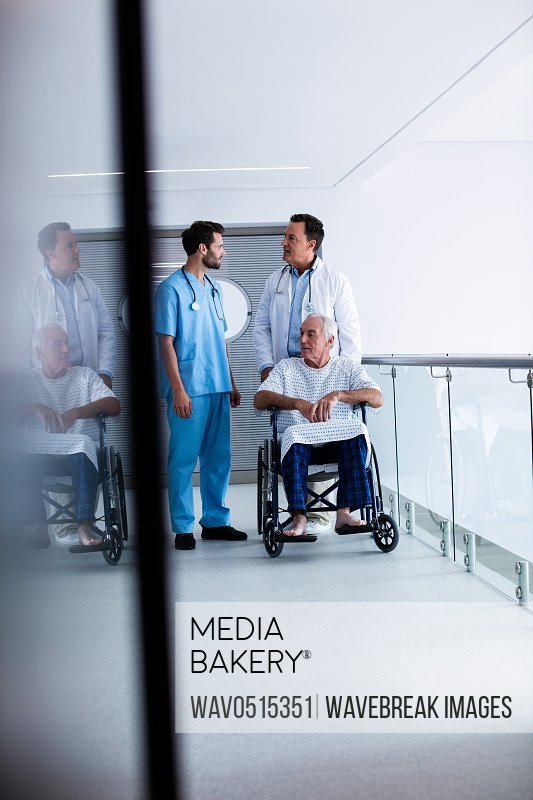 Doctors interacting with each other with patient on wheelchair in passageway