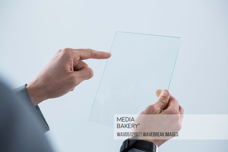 Businessman touching an glass sheet against white background