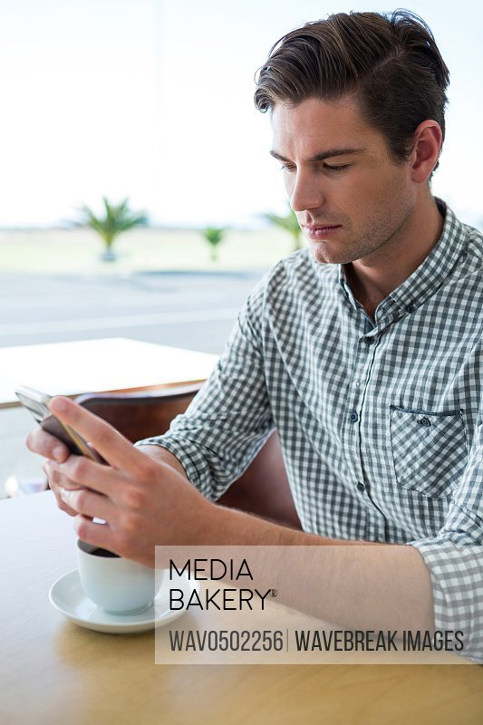 Man sitting at table and using his mobile phone in coffee shop