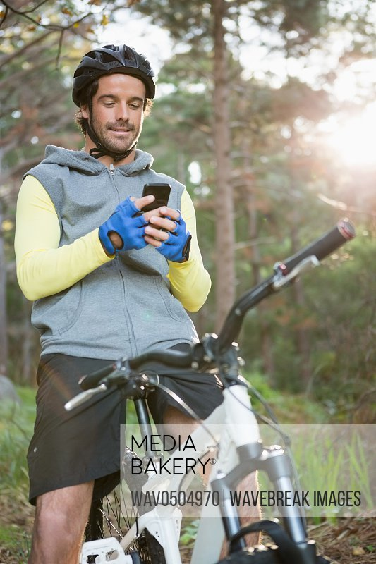 Mountain biker using mobile phone in the forest