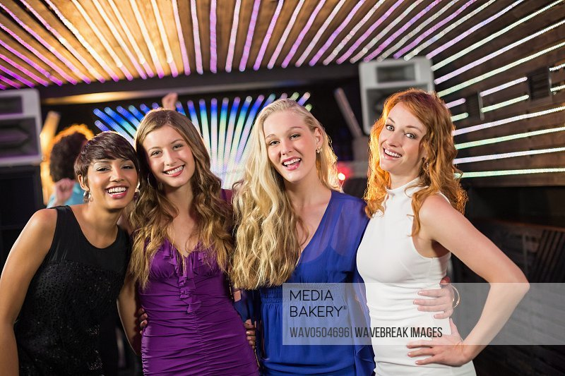 Portrait of smiling female friends standing together in bar