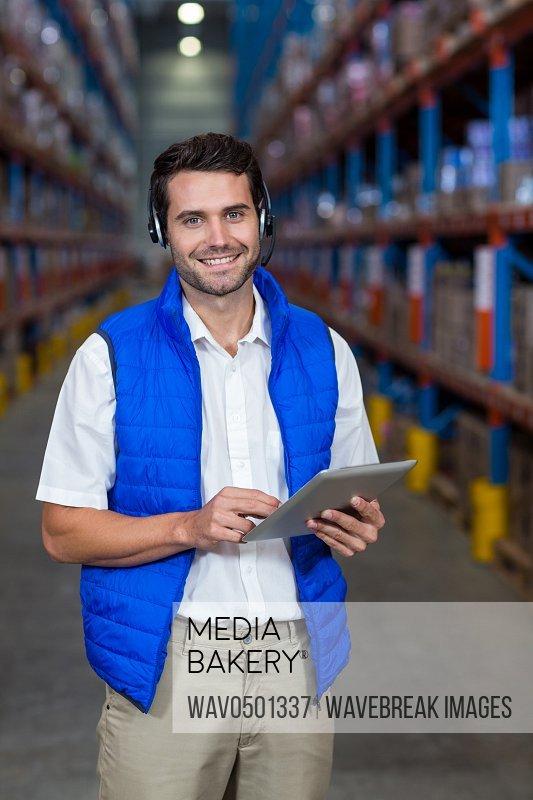 Portrait of warehouse worker holding digital tablet in warehouse