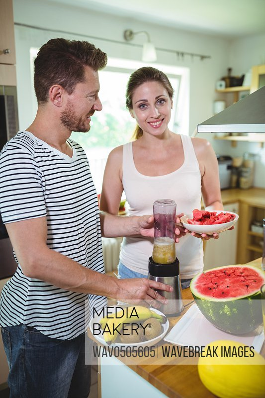 Smiling couple preparing fruit smoothie in kitchen at home