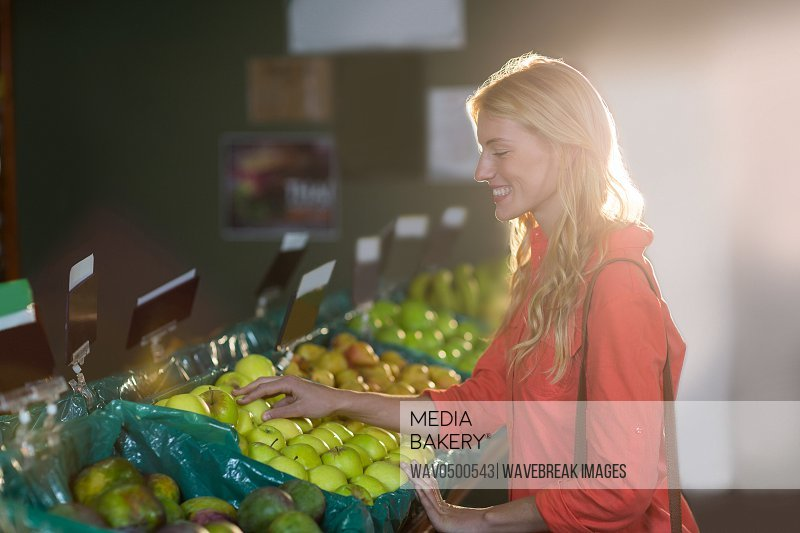 Smiling woman selecting green apples in organic section of supermarket