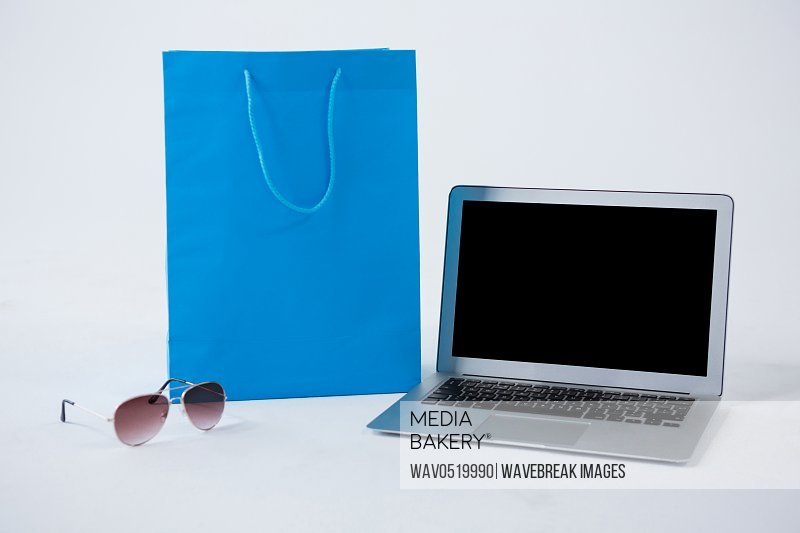 Shopping bag with sunglasses and laptop