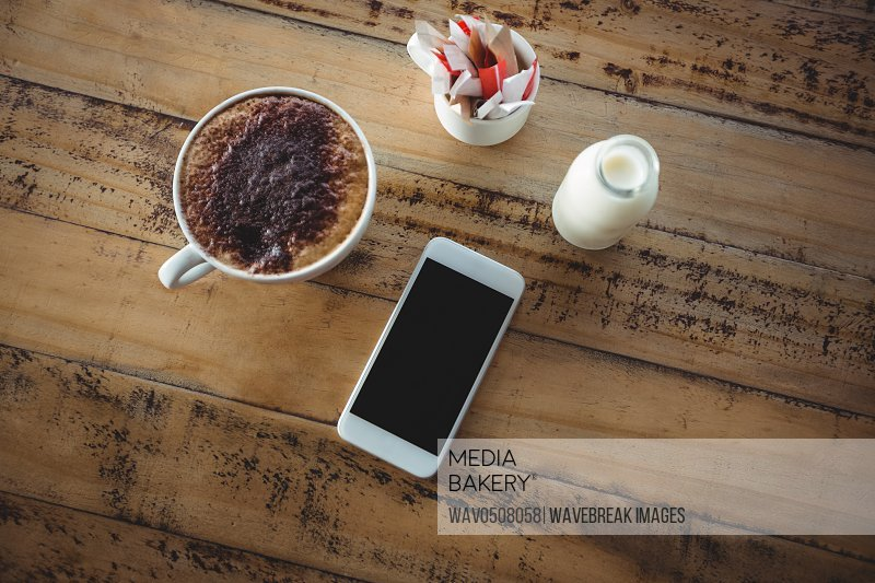 Coffee cup mobile phone and milk bottle on a table at cafA?