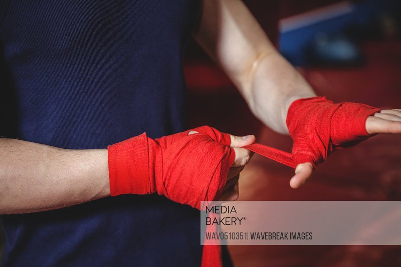 Mid-section of boxer wrapping boxing strap