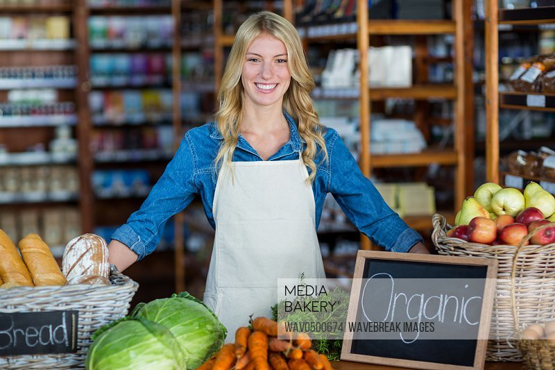 Portrait of smiling staff standing in organic section of supermarket
