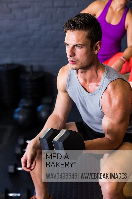 Determined male athlete exercising with dumbbell in fitness studio