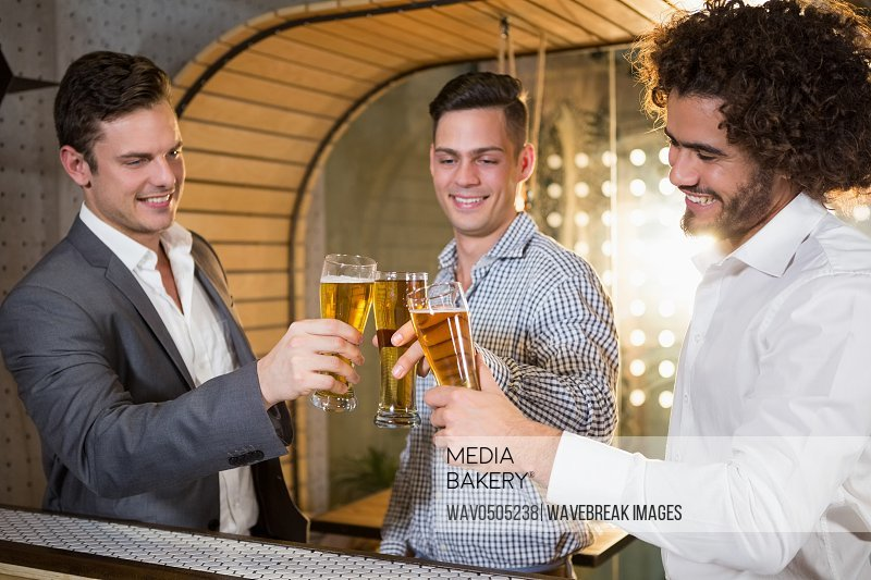 Group of friends toasting a glass of beer in bar
