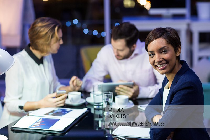 Businesswoman smiling with colleagues working in office at night