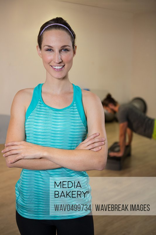 Portrait of smiling woman standing with arms crossed in fitness studio
