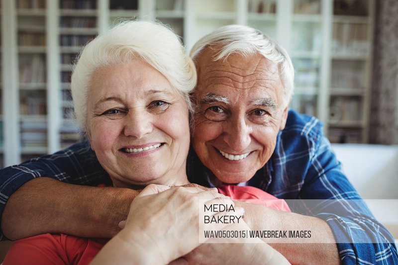 Portrait of senior couple embracing each other at home