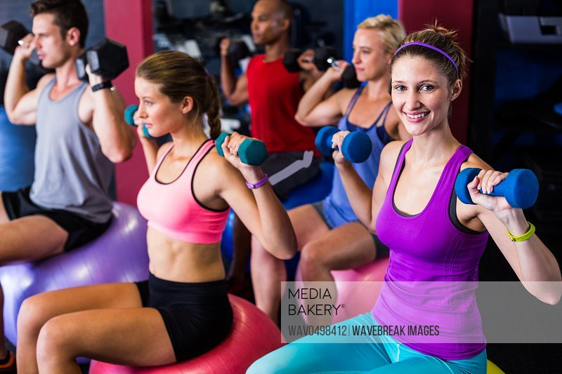 Friends lifting weights while exercising in gym