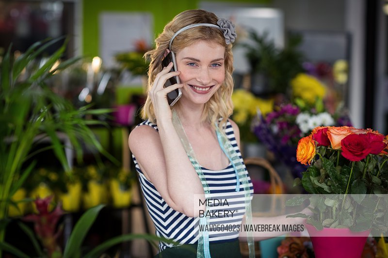 Female florist talking on mobile phone in the shop