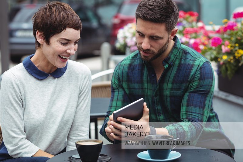 Businesspeople using digital tablet while having coffee in cafeteria