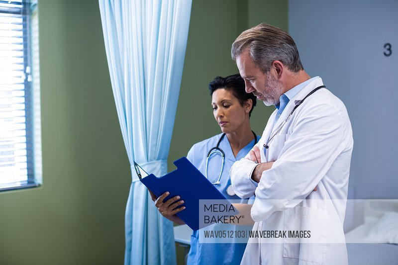 Doctor and nurse having discussion on file in ward of hospital