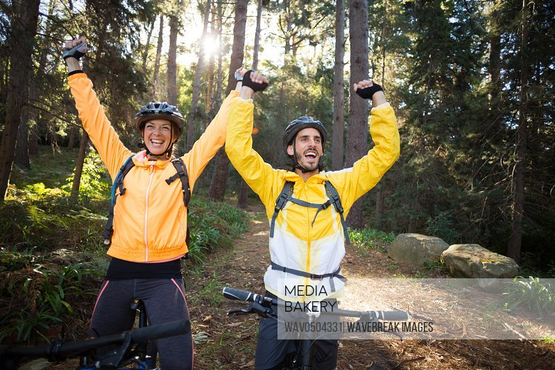 Excited biker couple with mountain bike in countryside forest
