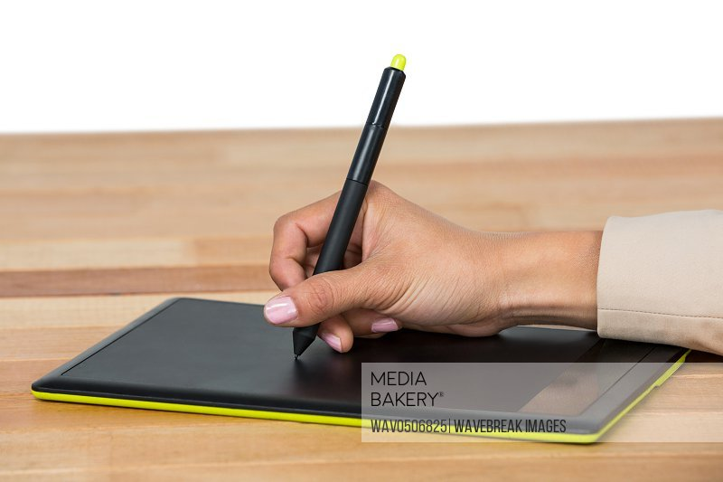 Hand of graphic designer using graphic tablet in office