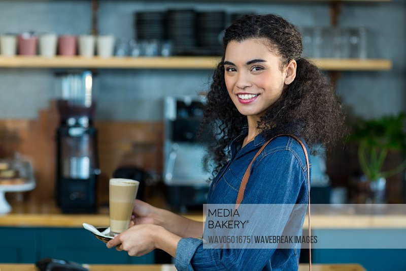Portrait of smiling woman holding a cup of coffee in cafA?