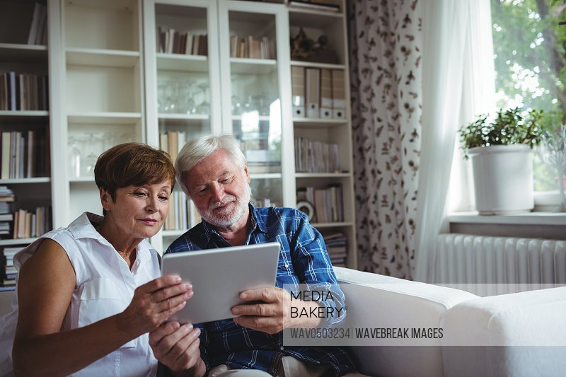 Senior couple sitting on sofa and using digital tablet in living room