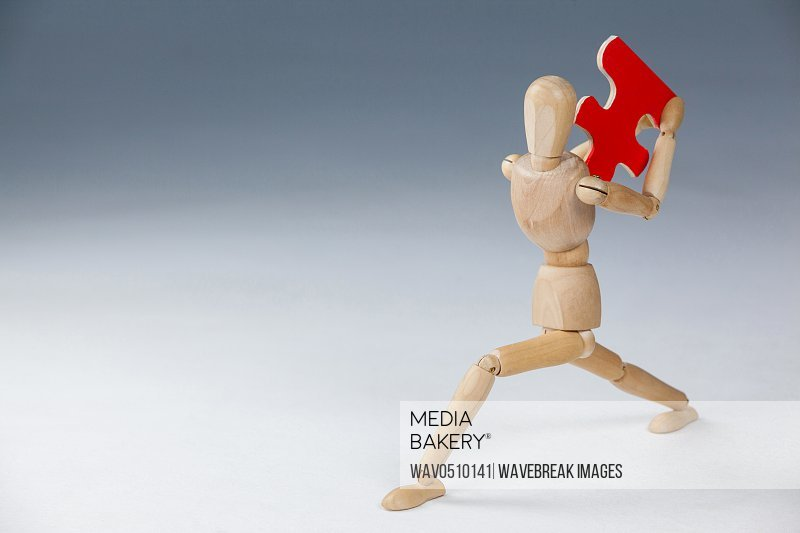 Wooden figurine holding a red puzzle piece against white background