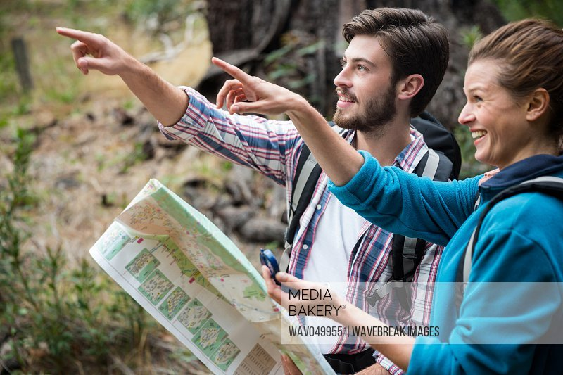 Hiker couple holding map and showing direction in forest