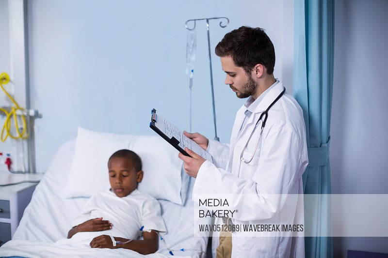 Doctor looking at report while patient sleeping on bed in hospital