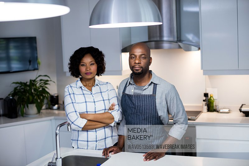 Portrait of couple embracing each other in kitchen