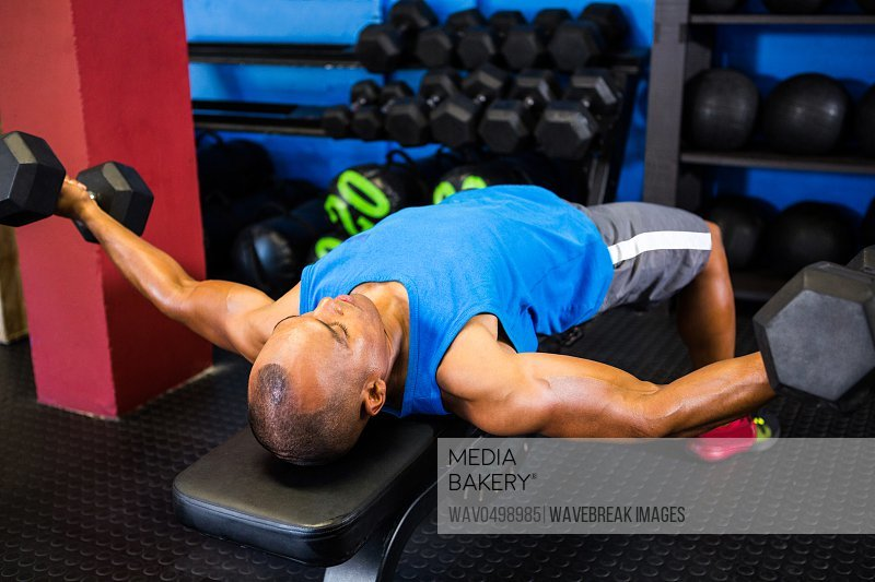 Man exercising with dumbbells on weight bench in fitness studio