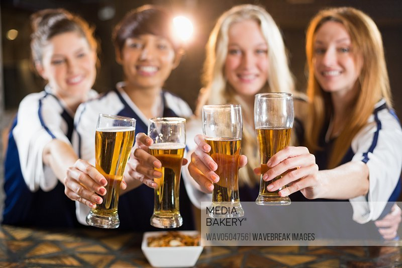 Portrait of smiling friends holding glass of beer in party at bar