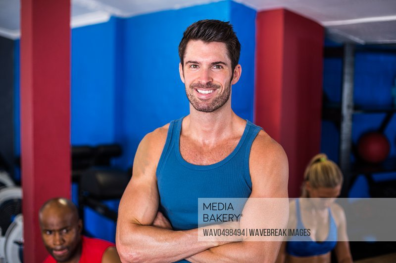 Portrait of smiling man with arms crossed while standing in gym