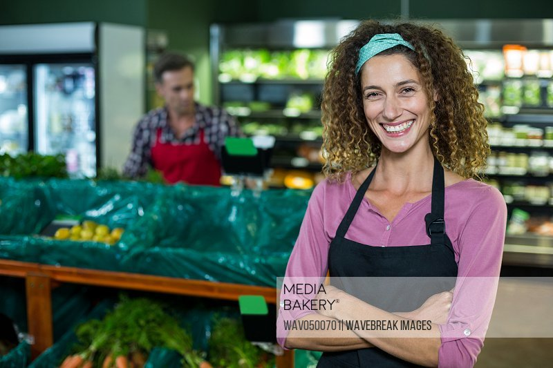 Portrait of smiling female staff standing with arms crossed in organic section of super market