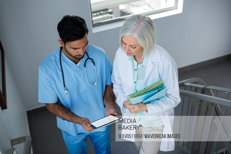 Doctors discussing over digital tablet while walking on stairs in hospital