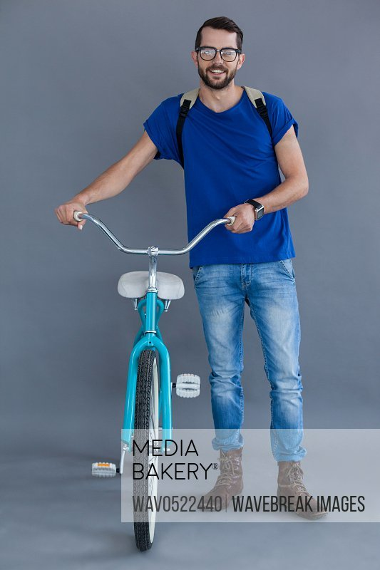 Man in blue t-shirt and backpack with a bicycle