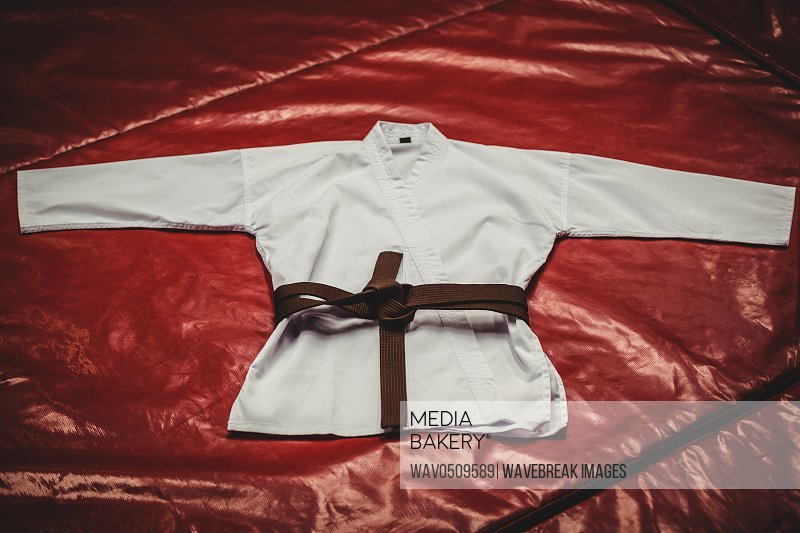 Karate uniform and brown belt on red background