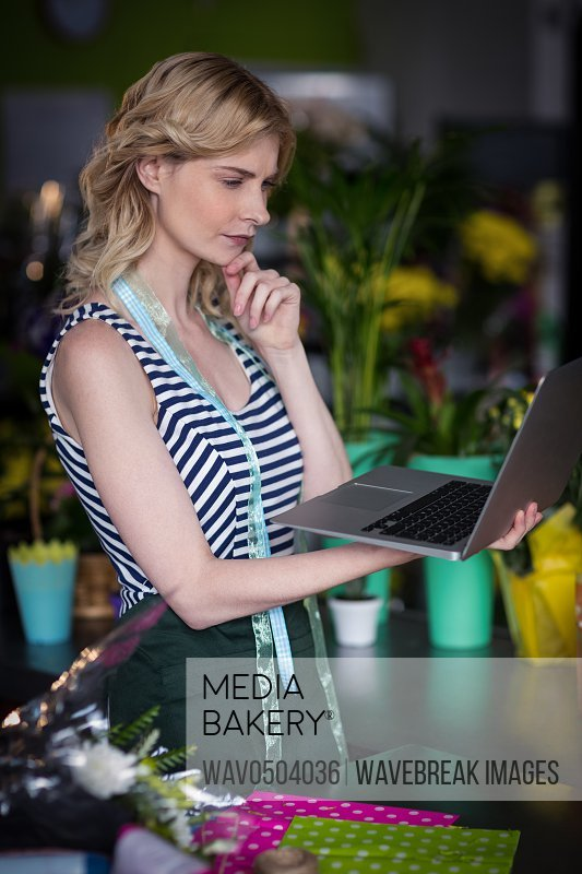 Thoughtful female florist looking at laptop in the flower shop