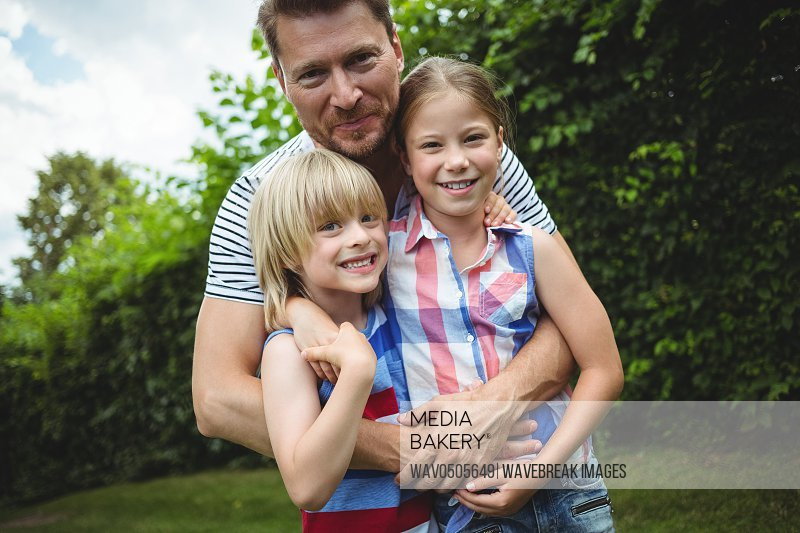 Father standing with their kids on grass in park on a sunny day
