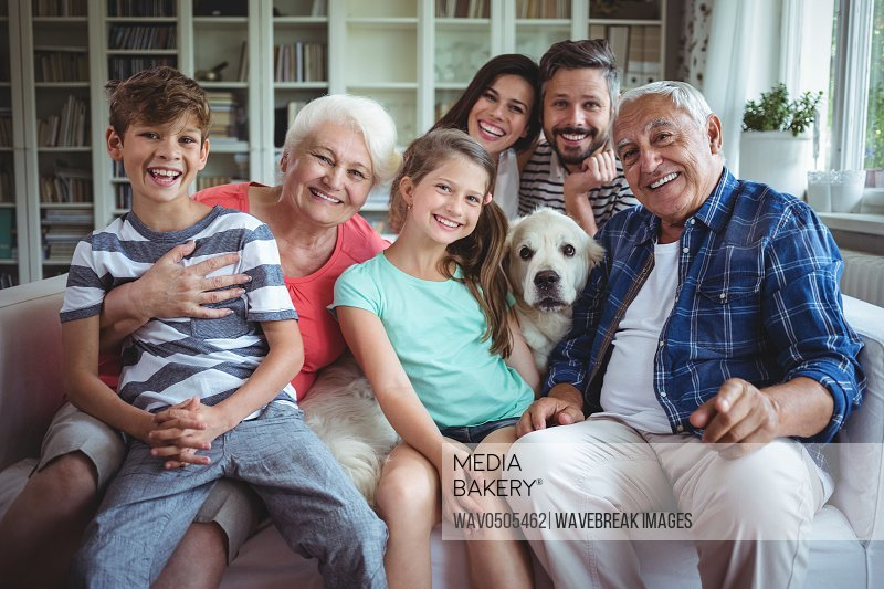 Portrait of happy multi-generation family sitting on sofa in living room at home