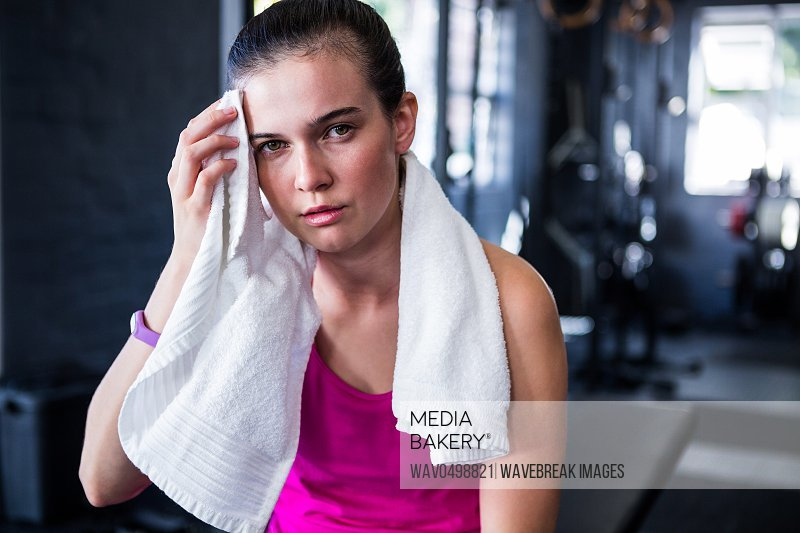 Portrait of young female athlete wiping sweat in gym