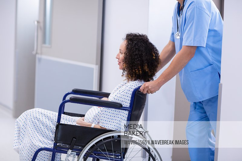 Doctor pushing a pregnant woman on wheelchair