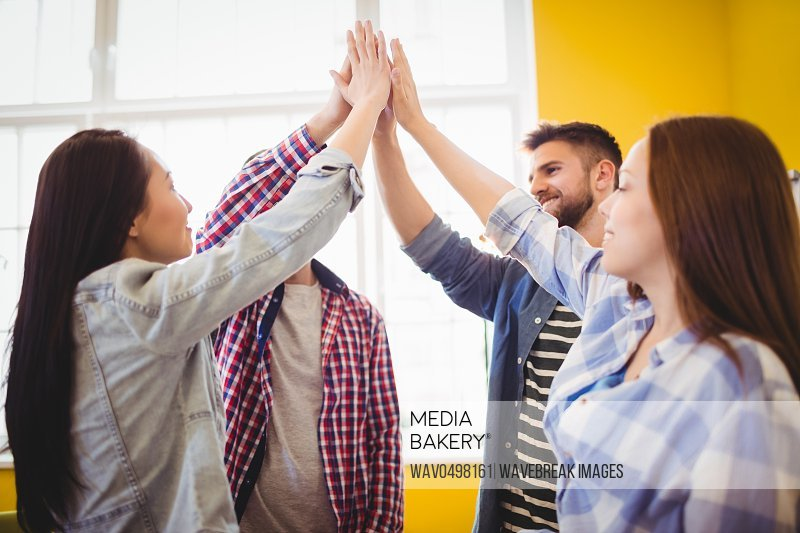Happy graphic team giving high-five in creative office