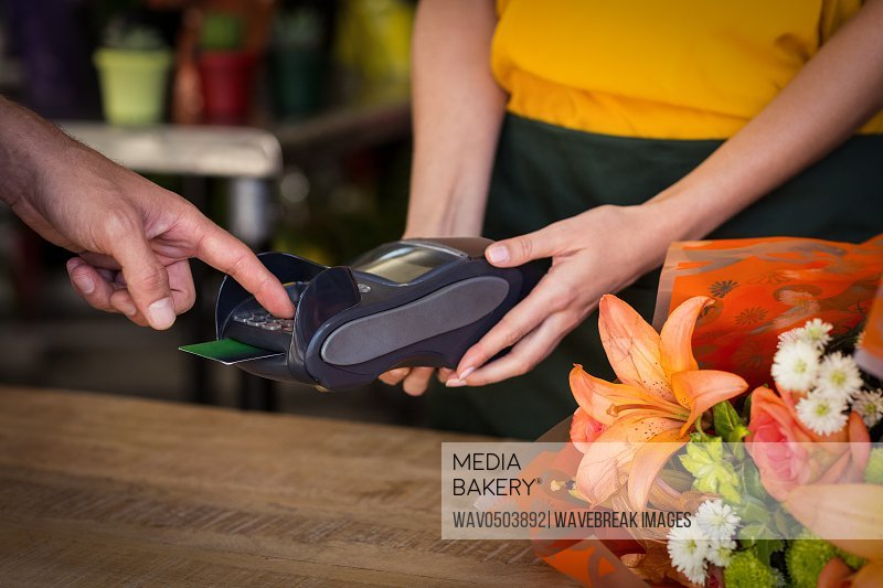 Man making payment with his credit card in the flower shop