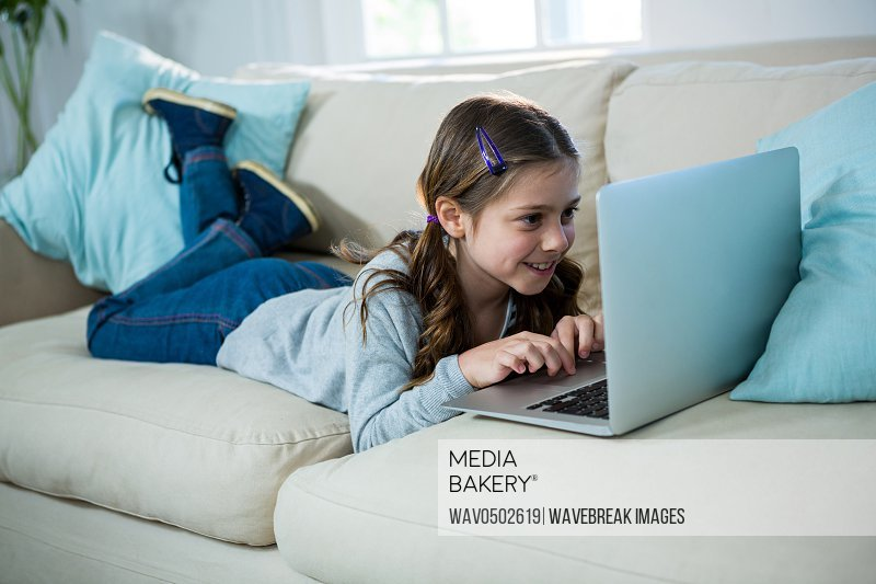 Girl relaxing on sofa and using laptop in the living room at home