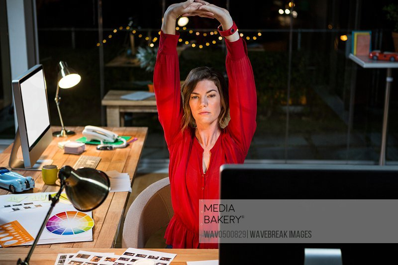 Businesswoman stretching hands at her desk in office