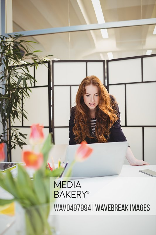 Young businesswoman using laptop in meeting at creative office