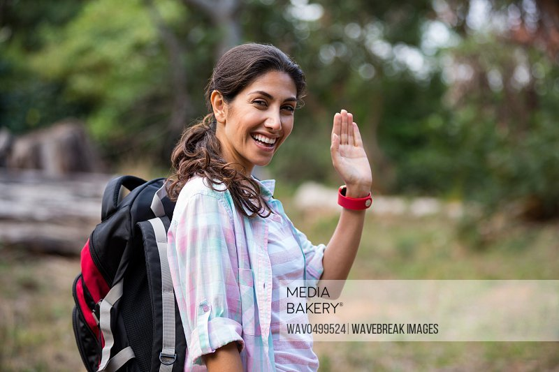 Portrait of female hiker waving hand while walking in forest