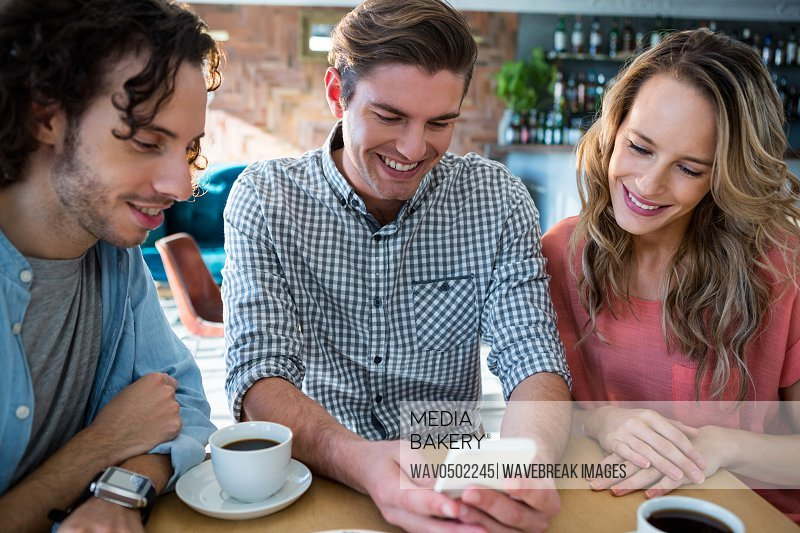 Smiling friends using mobile phone in coffee shop