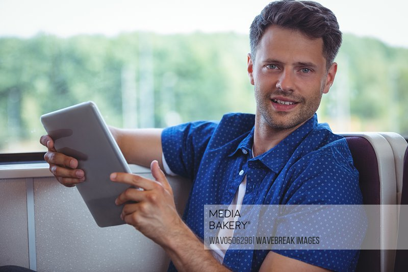 Portrait of handsome man using digital tablet while travelling in train